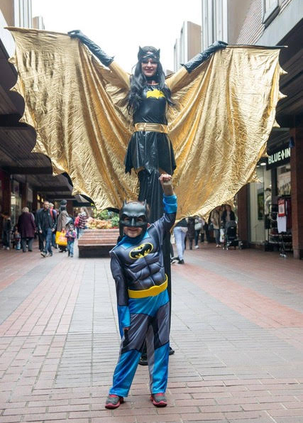 Superhero Bat Girl on Stilts